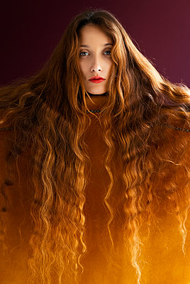 Portrait of young woman with long brown wavy hair leaning on golden chair against colored background - p300m2198943 by Tania Cervián