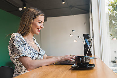 Smiling businesswoman working over laptop on table in cafe - p300m2251084 by MORNINGVIEW AGENCY