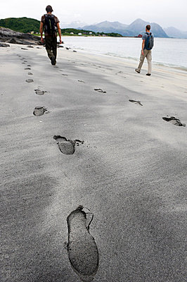 Two hikers walking on beach, footprints on foreground - p575m714889 by Fredrik Schlyter