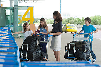 Family standing outside of airport with luggage - p623m659238f by Thierry Foulon