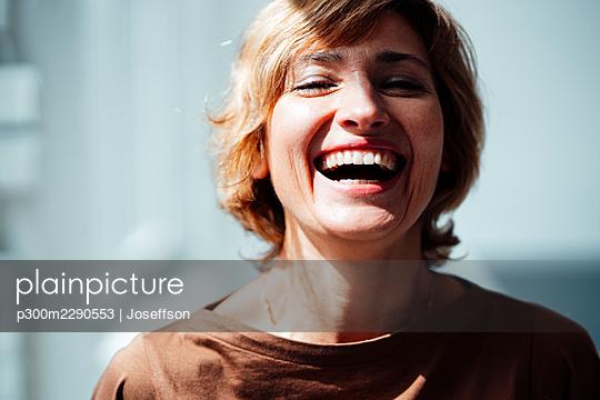 Sunlight on cheerful businesswoman in office - p300m2290553 by Joseffson