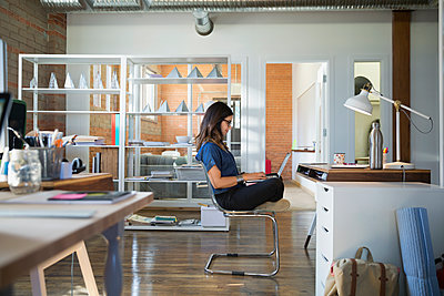 Creative businesswoman using laptop cross-legged in office - p1192m1145646 by Hero Images