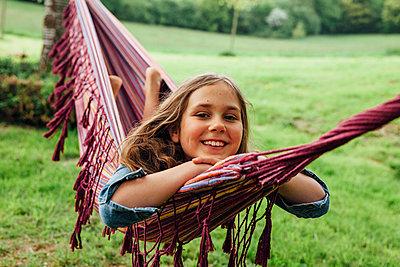 Portrait of happy girl lying in hammock - p300m1586945 von Annie Hall