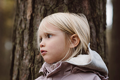 Portrait of blond little girl in front of tree trunk - p300m2140254 by Ekaterina Yakunina