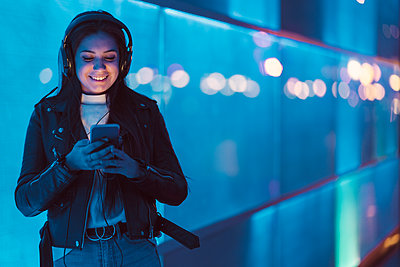Portrait of smiling teenage girl with headphones standing in front of blue glass pane looking at smartphone - p300m2166386 by Javier De La Torre Sebastian