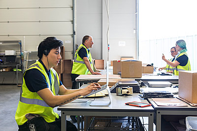 Confident young male customer service representative using laptop while coworkers discussing at desk in warehouse - p426m2018814 by Maskot
