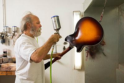 Guitar maker in workshop using spray gun to varnish guitar - p924m1206485 by Ian Spanier