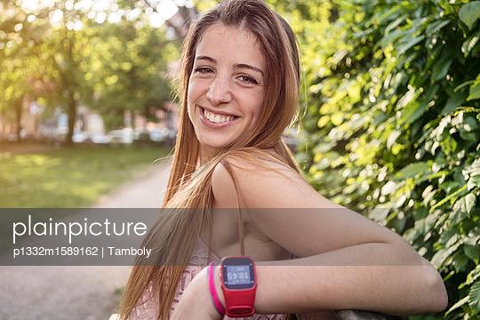 Junge Frau sitzt lachend auf einer Parkbank - p1332m1589162 von Tamboly