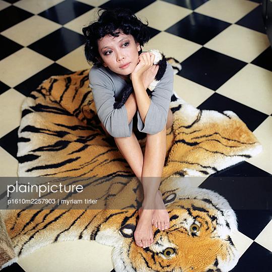 A woman sits on a fake tiger carpet  - p1610m2257903 by myriam tirler