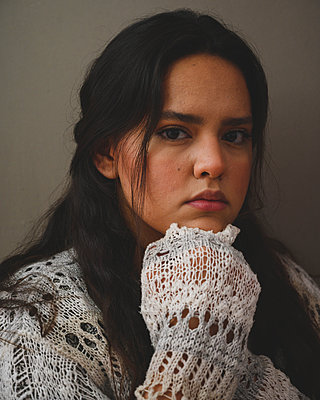 Portrait of a young beatiful hispanic woman on a grey background - p1166m2269213 by Cavan Images