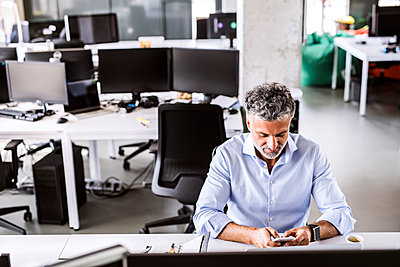 Mature businessman sitting at desk in office using smartphone - p300m1568070 by HalfPoint