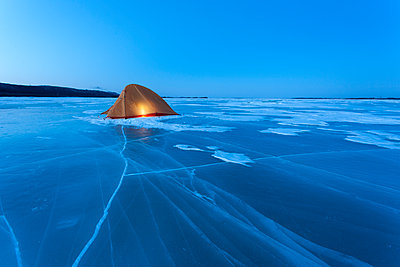 Russia, Amur Oblast, illuminated tent on frozen Zeya River at blue hour - p300m1568550 by Vasily Pindyurin