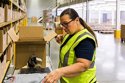 Side view of female worker packing cardboard box at warehouse - p426m2018877 by Maskot