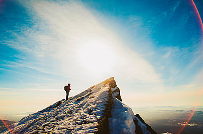 Man hiking on mountain in winter - p555m1305511 by Aleksander Rubtsov
