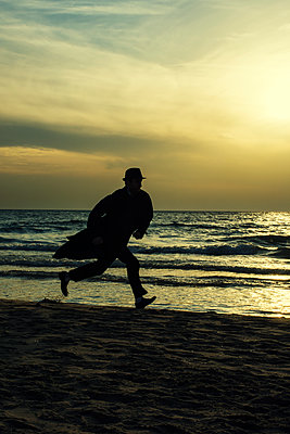 Silhouette of a male figure running on the beach at sunset  - p794m1508348 by Mohamad Itani