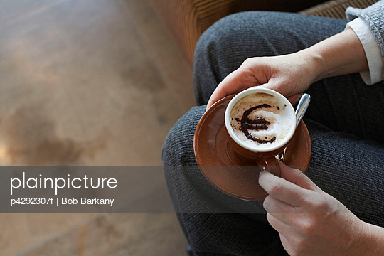 Woman holding cappuccino with euro motif - p4292307f by Bob Barkany