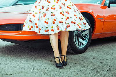 Frau im Petticoat-Kleid vor Oldtimer - p045m2089825 von Jasmin Sander