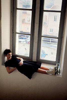 Woman in black dress and ice skates on the windowsill - p1105m2244912 by Virginie Plauchut