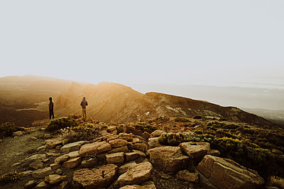 Two men stand on mountain top watching sunrise - p1166m2129917 by Cavan Images