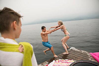 Playful woman pushing man off lake dock - p1192m1078336f by Hero Images
