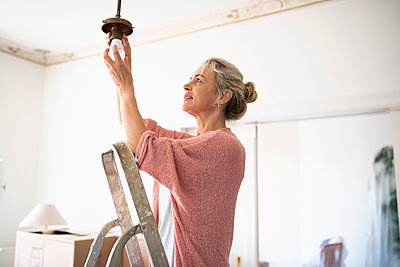 DIY woman changing light fixture - p1192m2016777 by Hero Images