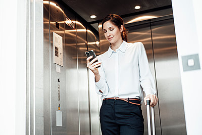 Businesswoman text messaging on mobile phone while standing in elevator - p300m2252317 by Joseffson