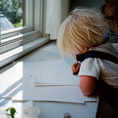 Boy sitting at window sill and drawing - p528m718607f by Johan Willner
