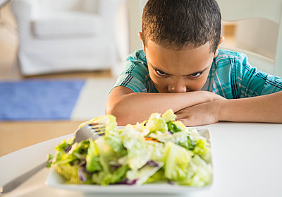 Mixed race boy refusing to eat salad - p555m1415558 by JGI/Jamie Grill