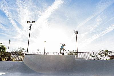 Hispanic man riding skateboard at skate park - p555m1444125 by Kolostock