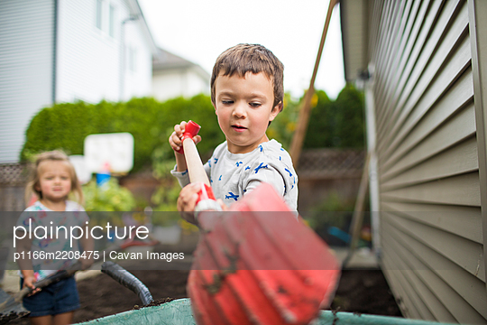 Young boy using red shovel in his backyard. - p1166m2208475 by Cavan Images