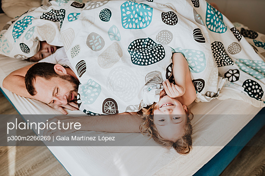 Smiling girl with father and brother lying on bed under blanket at home - p300m2266269 by Gala Martínez López