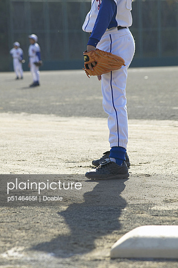 Boy in baseball uniform standing in field