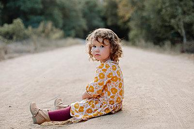 Full length of girl sitting on dirt road - p1166m1485335 by Cavan Images