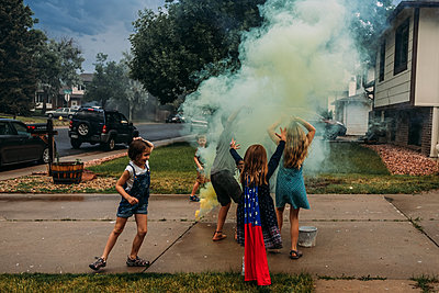 Children playing with a smoke bomb in a drive way on 4th of July - p1166m2157238 by Cavan Images