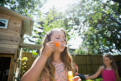 Girl blowing bubbles in sunny backyard - p1192m1183937 by Hero Images