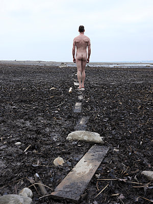 Naked man walks in the swamp on a narrow path - p1383m1548163 by Wolfgang Steiner