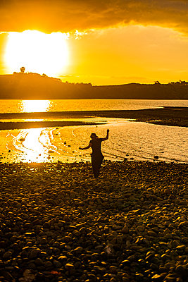 Woman on the waterfront at sunrise - p1455m2204860 by Ingmar Wein