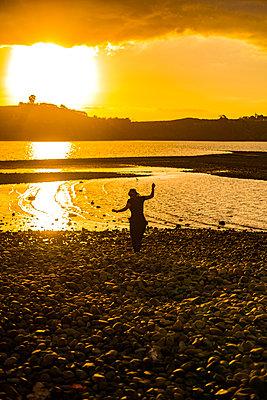 Frau an der Küste bei Sonnenaufgang - p1455m2204860 von Ingmar Wein