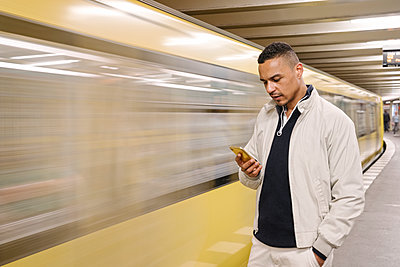 Portrait of man standing in front of driving underground train looking at cell phone, Berlin, Germany - p300m2143384 by Hernandez and Sorokina