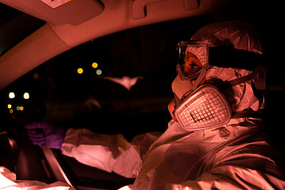 Senior woman wearing protective suit and mask driving car at night - p300m2170115 by Eloisa Ramos