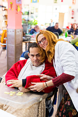 Smiling female caregiver with disabled man in nursing home - p300m2243791 by DREAMSTOCK1982