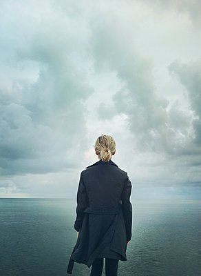 Frau im dunklen Mantel am Meer - p984m2022598 von Mark Owen
