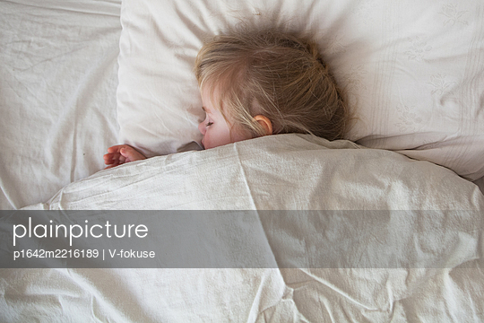 One year old baby sleeping in a white bed - p1642m2216189 by V-fokuse