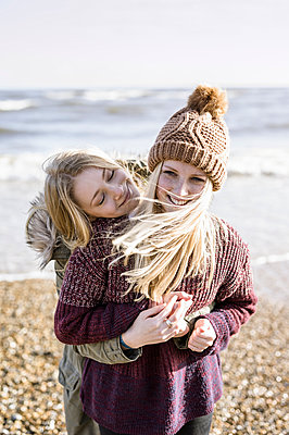 Two girls on the beach in winter. - p1100m906669f by Emily Hancock