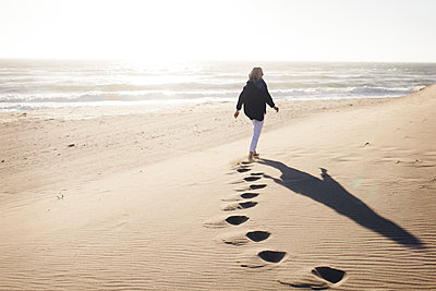 Rear view of senior woman walking on sand at beach against clear sky during sunny day - p1166m1509668 by Cavan Images