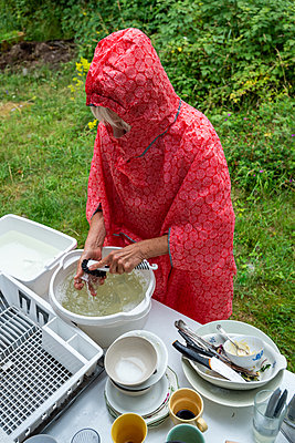 Woman in rain poncho washing up the dishes outdoors - p1418m2100795 by Jan Håkan Dahlström