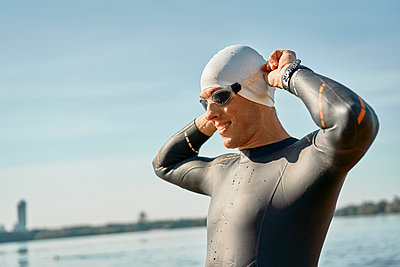 Sportsman in rubber cap and sports glasses standing on river - p1630m2203522 by Sergey Mironov
