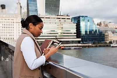 UK, London, businesswoman standing on bridge using cell phone - p300m1580890 von Mauro Grigollo