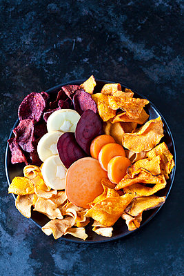 Sliced root vegetables and vegetable chips in bowl - p300m1581423 von Dieter Heinemann