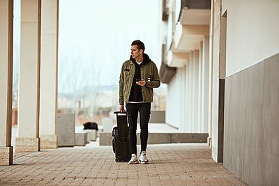 Man with suitcase holding mobile phone while looking away against sky - p300m2250061 by Aitor Carrera Porté